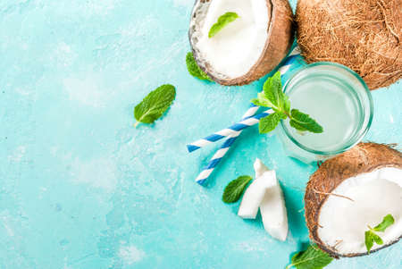 Healthy food concept.  Fresh Organic Coconut Water with coconuts, ice cubes and mint, on light blue background, copy space top view Stock Photo
