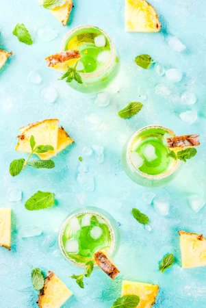 Tropical drink, Pineapple juice margarita cocktail with fresh mint, light blue background copy space top view