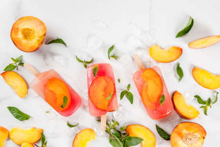 Summer desserts. Frozen drinks. Sweet fruit ice cream from frozen peach tea with mint. On a white marble table, with ingredients - peaches, mint, ice. Copy space top view Stock Photo