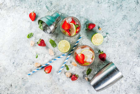 Summer refreshment drink, strawberry mojito cocktail on light concrete background, copy space