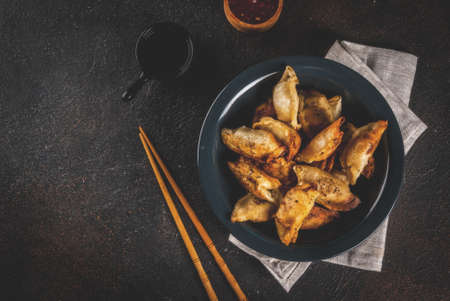 Fried asian dumplings Gyoza  on dark plate, served with chopsticks and soy sauce, dark background, copy space 免版税图像