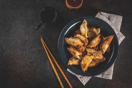 Fried asian dumplings Gyoza  on dark plate, served with chopsticks and soy sauce, dark background, copy space Фото со стока