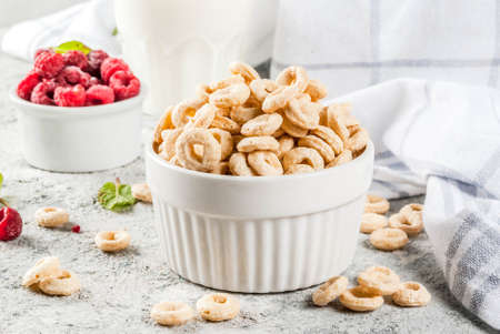 Healthy breakfast ingredients. Breakfast cereal corn rings, milk or yogurt glass, raspberries and mint on grey stone background, copy space