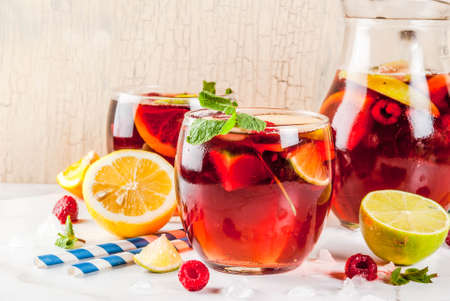 Summer cold cocktail, fruit and berry red wine sangria with apple, lemon, oranges and raspberry. light background, copy space Stock Photo