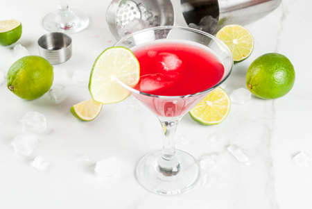 Red cosmopolitan cocktail with lime in martini glass, on white marble background copy space Фото со стока