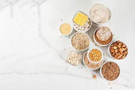 Selection various types cereal grains groats  in different bowl on white marble background, copy space above Фото со стока