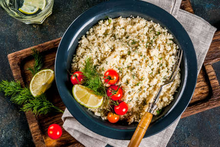 Light dietary food, couscous with tomatoes, lime and fresh herbs in dark bowl, dark blue background copy space top view