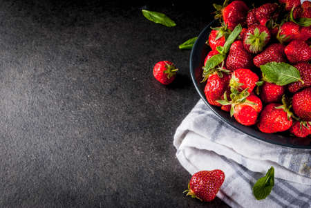 Fresh raw organic strawberry, dark stone background copy space top view Imagens