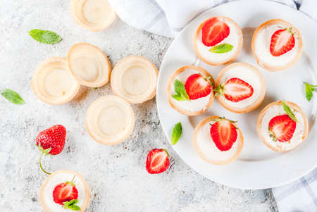 Summer sweet homemade dessert, Mini cheesecakes with strawberry on grey stone table copy space top view