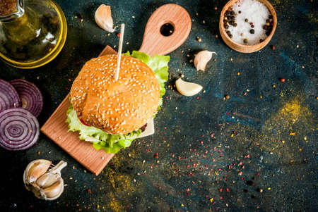 Fast food. Unhealthy food. Delicious Fresh Tasty Burger with Beef Cutlet, fresh Vegetables and Cheese on dark blue concrete background. Copy space top view Stok Fotoğraf