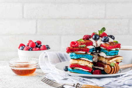 American Independence Day July 4th breakfast idea, homemade white blue red striped pancakes with fresh whipped cream, berry and honey, morning light grey stone background copy space