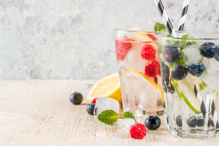 Various berry lemonade or mojito cocktails, fresh iced lemon lime raspberry blueberry infused water, summer healthy detox drinks light background copy space Stock Photo