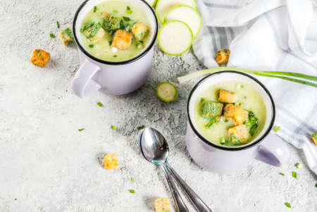 Two portions of homemade zucchini creamy soup with bread crumbs in mugs on a light concrete background. top view Banque d'images - 101255110