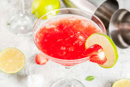 Cold strawberry margarita cocktail with ice, lime and fresh berries in margarita glass, light grey background copy space  写真素材