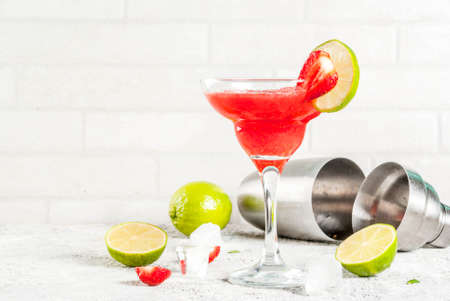 Cold strawberry margarita cocktail with ice, lime and fresh berries in margarita glass, light grey background copy space  Stock Photo