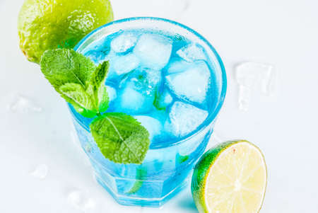Colorful summer beverage, iced blue  alcohol cocktail drink with lime and mint, white marble background copy space Stock Photo
