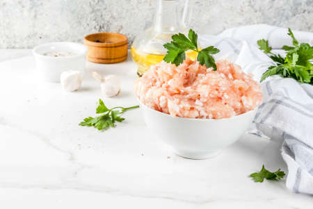 Raw chicken or turkey minced meat in white bowl,  with oil, spices and herbs on light background. Copy space.