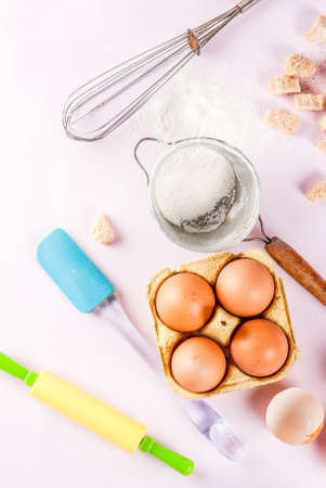 Ingredients and utensils for cooking baking egg, flour, sugar, whisk, rolling pin, on light pink background, top view