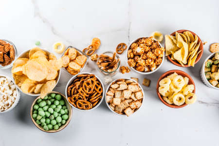 Variation different unhealthy snacks crackers, sweet salted popcorn, tortillas, nuts, straws, bretsels, white marble background copy space Stock Photo