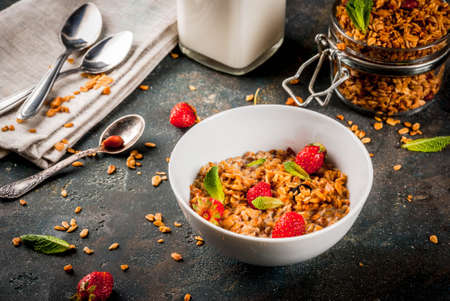 Homemade granola from mix of cereals (barley, oat, rye, bran) with with strawberry, mint leaves and fresh organic milk on dark blue concrete background