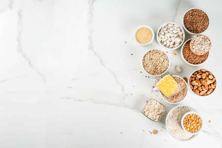 Selection various types cereal grains groats  in different bowl on white marble background, above copy space