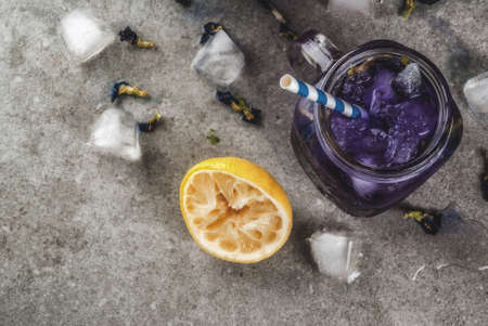 Healthy summer cold beverage, iced organic blue and violet butterfly pea flower tea with limes and lemons, grey concrete background copy space top view 版權商用圖片 - 101720210