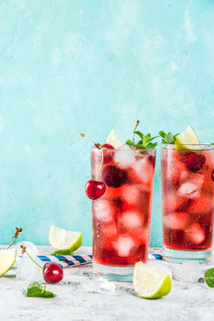 Summer iced refreshment drink, cherry cola lemonade or mojito cocktail in tall glass, on light blue and grey background copy space 스톡 콘텐츠