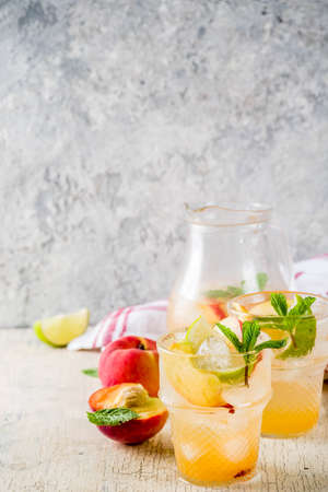 Peach and lime lemonade, mojito cocktail with fresh fruit garnish, om light concrete background copy space selective focus Stock Photo