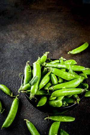 Raw fresh green pea in black bowl, dark rusty background copy space Stock Photo