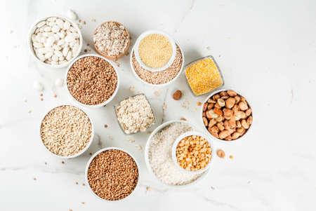 Selezione vari tipi di chicchi di cereali semole in diversi recipienti su marmo bianco sullo sfondo, copia spazio vista dall'alto