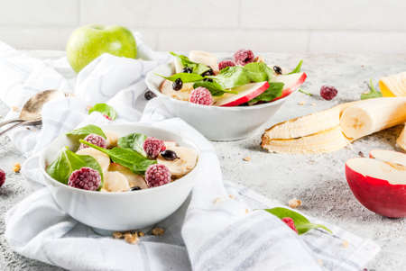 Healthy summer breakfast, fruit and berry salad with spinach, granola, apple and banana, white marble background  copy space