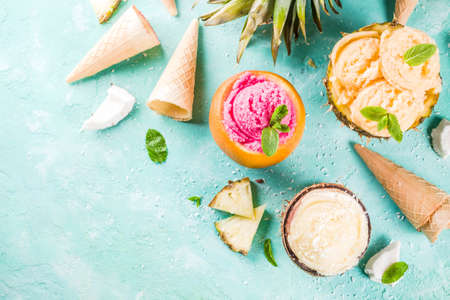 Summer holiday vacation concept, set various tropical ice cream sorbets, frozen juices in pineapple, grapefruit and coconut, light blue concrete background copy space
