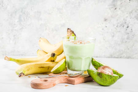Healthy summer drink, avocado and banana smoothie with lime, granola and coconut milk, dark rusty background copy space