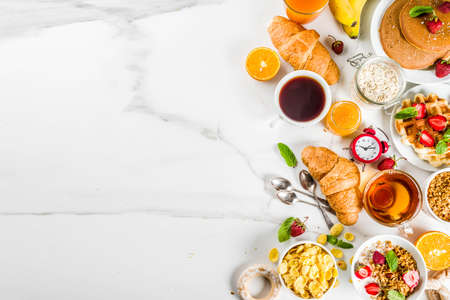 Healthy breakfast eating concept, various morning food - pancakes, waffles, croissant oatmeal sandwich and granola with yogurt, fruit, berries, coffee, tea, orange juice, white background Foto de archivo