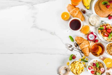 Sana colazione mangiare concetto, vari cibi mattutini - frittelle, cialde, panino di farina d'avena croissant e muesli con yogurt, frutta, frutti di bosco, caffè, tè, succo d'arancia, sfondo bianco