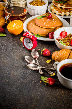 Healthy breakfast eating concept, various morning food - pancakes, waffles, croissant oatmeal sandwich and granola with yogurt, fruit, berries, coffee, tea, orange juice, dark rusty background