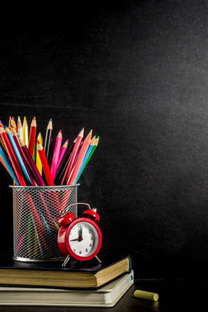 Back to school concept with books, alarm clock, color pencils, chalkboard background