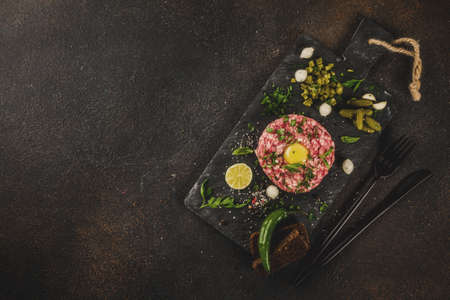 French cuisine, beef steak tartare with raw quail egg yolk, pickled cucumber and onions, fresh herbs, bread, dark rusty background copy space top view