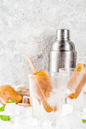 Frozen refreshing drinks, summer cocktail popsicles recipe, cuba libre, cold sweet tea or coffee, with ice, lime and mint leaves on white marble background copy space