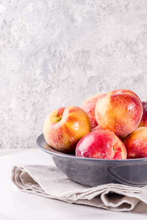 Raw fresh peaches in bowl on grey concrete background copy space Фото со стока - 102405427