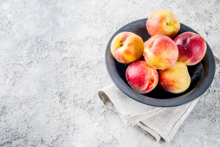 Raw fresh peaches in bowl on grey concrete background copy space