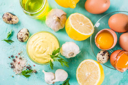 Homemade mayonnaise sauce with ingredients - lemon, eggs, olive oil, spices and herbs, light blue background copy space above