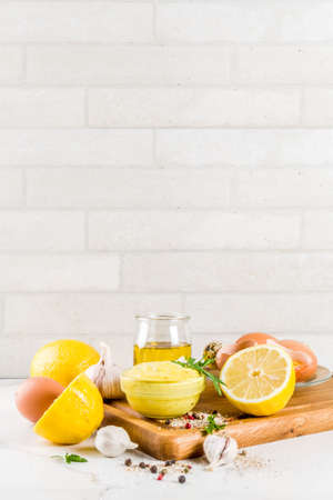 Homemade mayonnaise sauce with ingredients - lemon, eggs, olive oil, spices and herbs, white marble kitchen table copy space