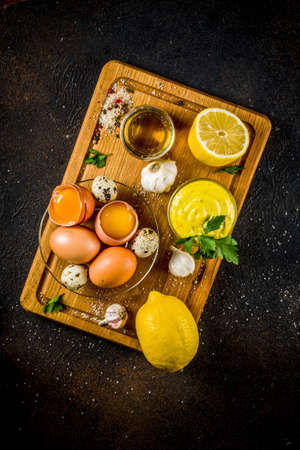 Homemade mayonnaise sauce with ingredients - lemon, eggs, olive oil, spices and herbs, black concrete background copy space