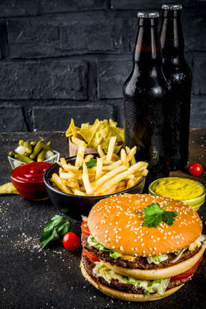 Various party food, Hamburgers, French fries, potato chips, pickled cucumbers, onions, tomatoes and cold beer bottles, rusty black concrete background copy space Banco de Imagens - 102490406