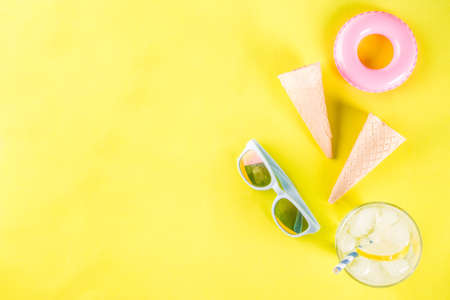 Summer holidays vacation concept background, hat, sunglasses, cooling drink (lemonade, mojito) with ice, ice cream cones, Lifebuoy yellow background copy space flatlay above