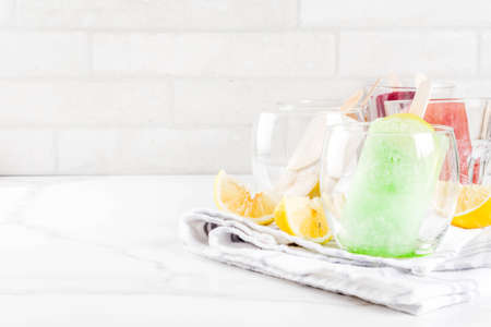 Summer party food ideas, frozen boozy alcohol cocktails popsicles - Prosecco, Vodka lime mojito, Champagne, Bellini, Margarita, Negroni etc white marble table copy space