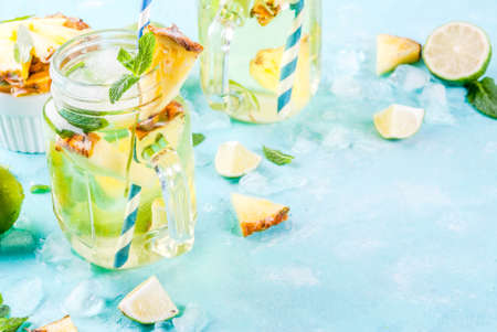 Tropical drink,  Pineapple mojito or lemonade with fresh lime and mint  light blue background, copy space