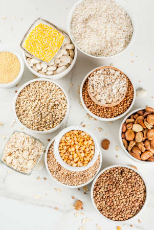 Selection various types cereal grains groats  in different bowl on white marble background, close top view