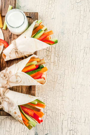 Summer healthy snack appetizer, Mexican style tortilla sandwich wraps assorted colorful fresh vegetable sticks (celery, rhubarb, pepper, cucumber and carrot) with yoghurt sauce dip above